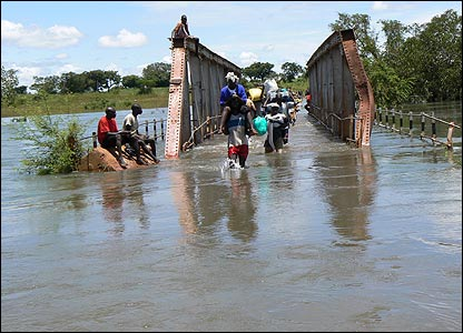People walking over flooded Aswa bridge [Pic: Hudson Apunyo]