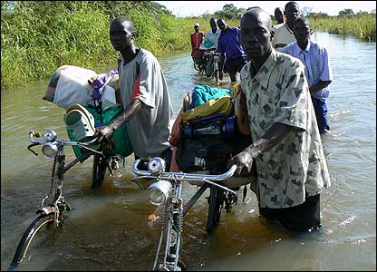 People pushing bicycles through the flooded River Moroto [Pic: Hudson Apunyo]