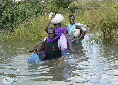 People carrying bundles of their belongings on their heads crossing River Moroto [Pic: Hudson Apunyo]