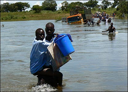 Man carrying a woman and a bucket crossing Aswa River [Pic: Hudson Apunyo]
