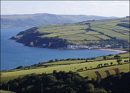 the coastal village in the distance at the foot of the Glens of Antrim