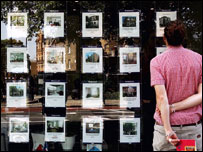 A man looking into an estate agent's window