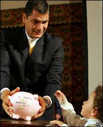 Child puts coin in piggy bank held by Ecuador President Rafael Correa