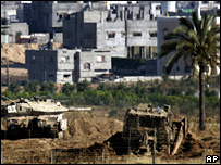 An Israeli tank and bulldozer take up position inside Gaza