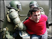 A demonstrator is arrested by riot police during a protest march 9 September 2007 in Santiago for the 34th anniversary of the 11 September 1973 military coup d'etat in Chile