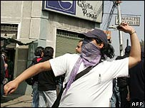A demonstrator throws stones during a protest march 9 September 2007 in Santiago for the 34th anniversary of the 11 September 1973 military coup d'etat in Chile