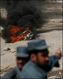 Afghan policeman near a vehicle which caught fire after a suicide attack on a convoy of French troops in  Kabul, Afghanistan