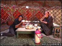 Two Kazak women eating food in a yurt hut