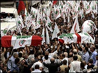 Coffins being carried through crowds