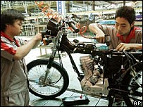 Workers assemble motorcycle at a factory in China