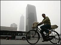 A cyclist and a bus pass by the high rise buildings shrouded in a haze of smog, in Beijing