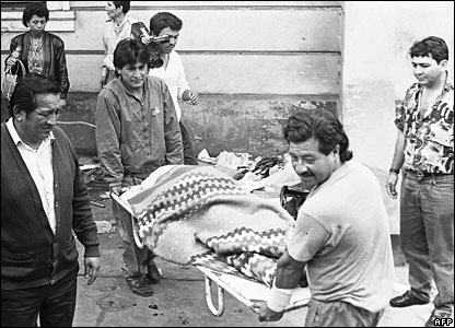 Policemen carry the body of one of 15 people killed at a barbecue in Lima, Peru in November 1991 (file)