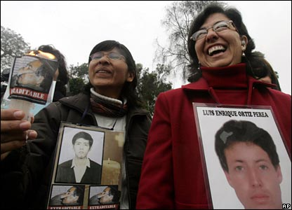 Relatives of people killed at La Cantuta university, during the government of former President Alberto Fujimori, holds photos of family members as they celebrate Fujimori's extradition in Lima