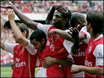 Emmanuel Adebayor (cente) is mobbed by his team-mates