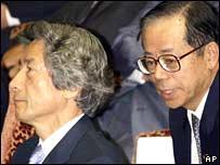 Chief Cabinet Secretary Yasuo Fukuda, (R), whispers to Japanese Prime Minister Junichiro Koizumi in July 2002