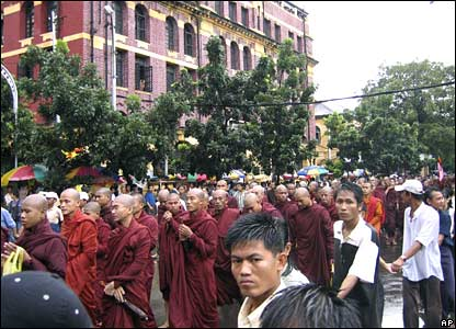 Onlookers link arms to protect Buddhist monks during an anti-junta protest in Rangoon on Sunday 23 September 2007