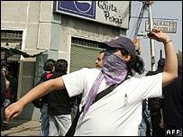 Un manifestante arroja una piedra a cara tapada