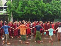 Onlookers holding hands as monks walk by