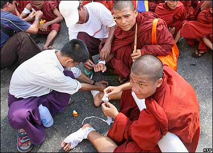 Buddhist monks receive treatment for injuries from walking barefoot in the streets in central Rangoon, 25 September 2007