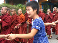 A female protester joins hands with others marching alongside monks (Photo: Ko Htike)