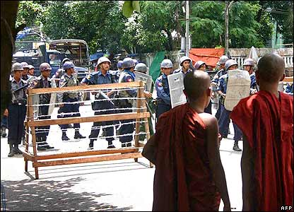Buddhist monks (R) look on as armed police block off a street in downtown Rangoon, 26 September, 2007
