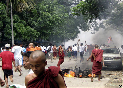 Photograph from Burmese opposition group, the National League for Democracy-Liberated Area, showing monks and protesters running past a burning motorcycle in Rangoon on 26 September, 2007