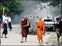 Monks pass a burning motorcycle in Rangoon on 26 September