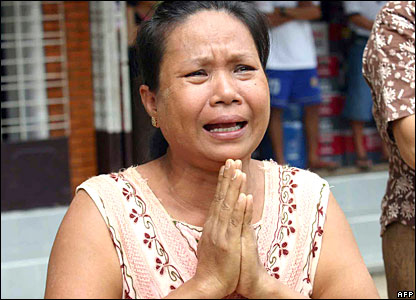 A woman prays for monks during protests in Rangoon, Burma