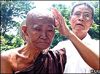 An elder Buddhist monk is escorted on the side of the street by a protester in a street in downtown Yangon, 26 September 2007