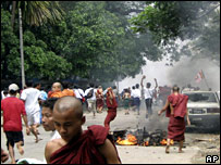 Buddhist monks and Burmese people run past a burning motorcycle in Rangoon