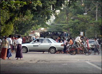 protesters and army trucks in central Rangoon.