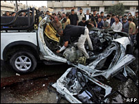 Crowds examine the remains of the vehicle destroyed in the Gaza strike