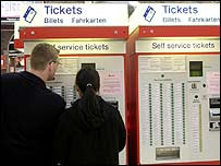 Customers at rail ticket machine