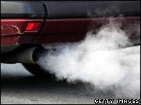 Un auto emite gases.