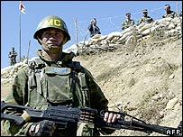 Georgian soldier in South Ossetia, watched by Russian troops