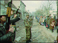 Yugoslav troops beside a column of refugees in Vukovar, 1991