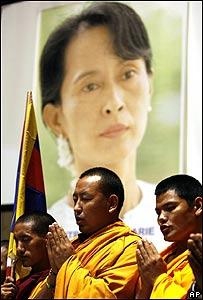 Monjes budistas rezan en Roma, Italia, delante de de un cartel con la imagen de Aung San Suu Kyi