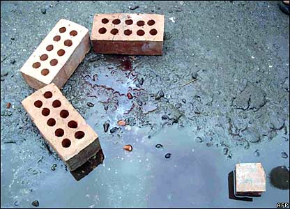 An injured monk's blood stains next to bricks after Burmese security forces stormed a monastery in Rangoon on Thursday 27 September 2007