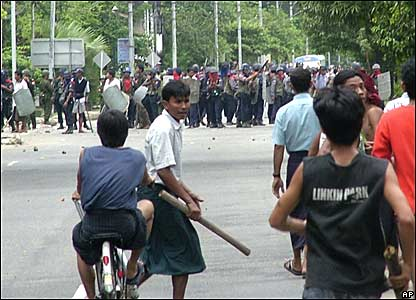 Demonstrators carry pieces of wood as they face riot policemen in Rangoon on Thursday 27 September 2007