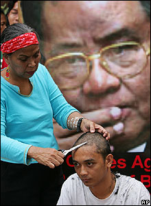 Man has his head shaved in front of a poster of Than Shwe in the Philippines - 28/09/07