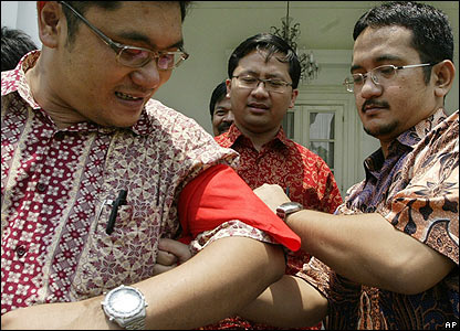 Indonesian foreign ministry workers tie red bands around their arms for a protest in Jakarta - 28/09/07