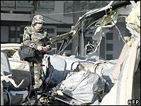 French soldier stands in the wreckage of a bus in Kabul after Saturday's bombing