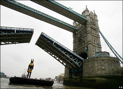A statue of the ancient Egyptian god of the dead, Anubis, passes under Tower Bridge in London