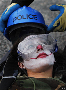 Police put a protective helmet and goggles on a protester before cutting her free during the last day of a year-long anti-nuclear protest outside the Faslane Naval Base in Scotland