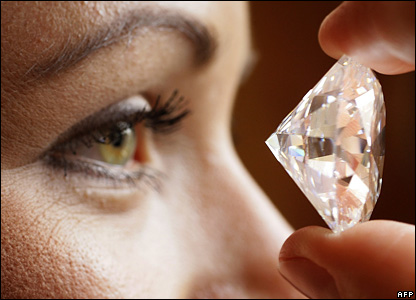 An employee of the auction house Sotheby's in Geneva holds up the largest brilliant-cut D-colour flawless diamond ever to appear at auction.