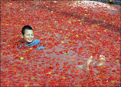 An Israeli boy splashes around in a pool of tomatoes at a tomato festival at Hevel Shalom in the western Negev region of Israel