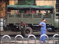 A woman passes a military vehicle in Rangoon on Monday