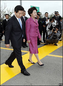 Mr Roh and his wife walk across a yellow line dividing the two Koreas