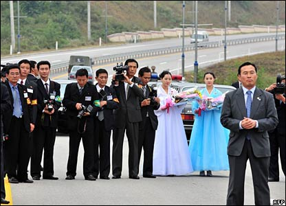 North Korean officials and journalists wait on the North side of the border