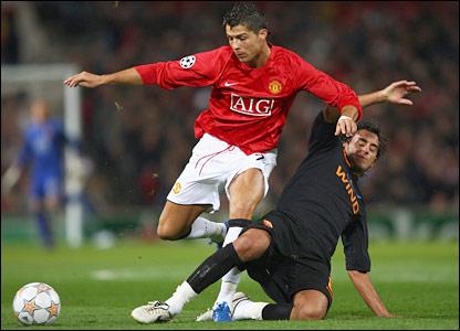 Roma's Alberto Aquilani challenges Cristiano Ronaldo